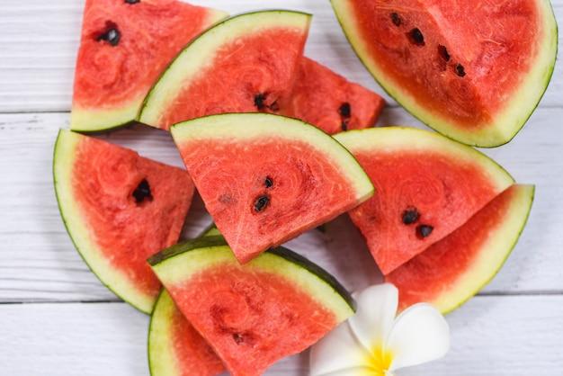 Fond de tranche de pastèque fraîche / fruits d'été pastèque et fleur blanche