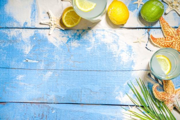 Fond tropical de vacances de vacances d'été avec des boissons de limonade. cocktail mojito avec des ombres claires et sombres, sur un fond tropical avec des étoiles de mer, des feuilles de palmier copient l'espace pour le texte