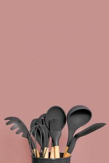 Fond d'ustensiles de cuisine avec fond, concept de décoration de cuisine à domicile, ustensiles de cuisine, accessoires en caoutchouc dans un récipient.