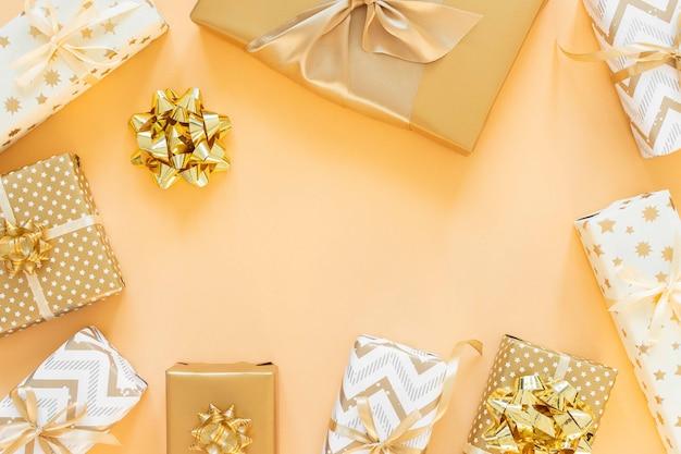 Fond de vacances aux couleurs dorées, coffrets cadeaux avec des arcs sur fond doré, mise à plat, vue de dessus, espace pour copie