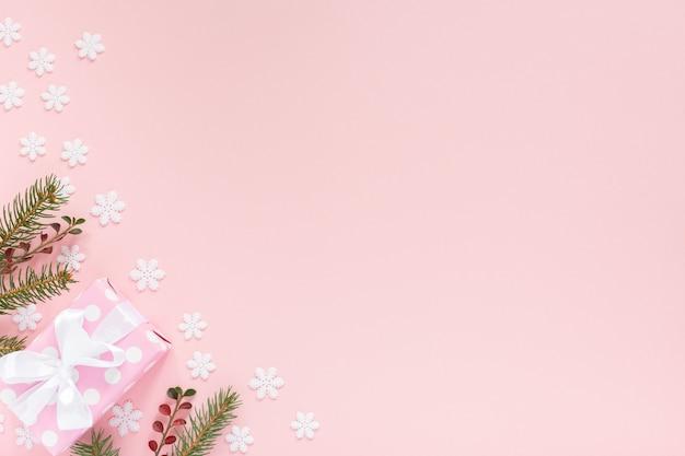 Fond de vacances, boîte-cadeau rose à pois avec ruban blanc et arc et branches d'épinette sur fond rose avec des flocons de neige, mise à plat, vue de dessus