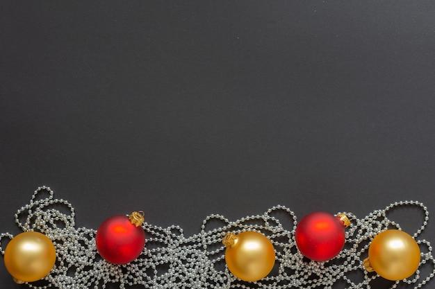Fond de vacances, boules de noël rouges et or et perles décoratives en argent sur fond noir, mise à plat, vue du dessus