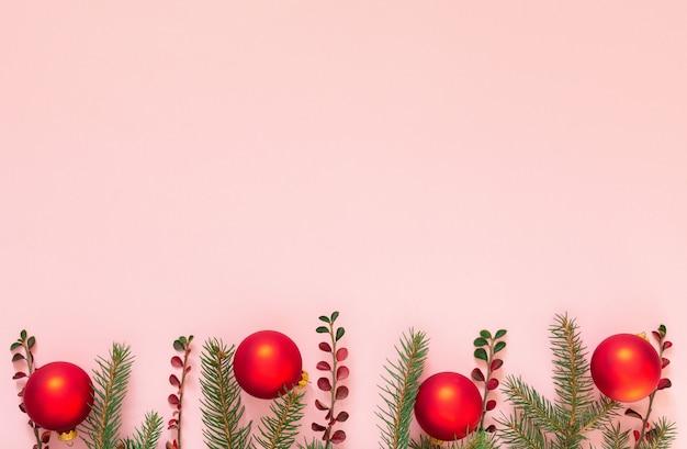 Fond de vacances, branches d'épinette et boules de noël sur fond rose, mise à plat, vue de dessus