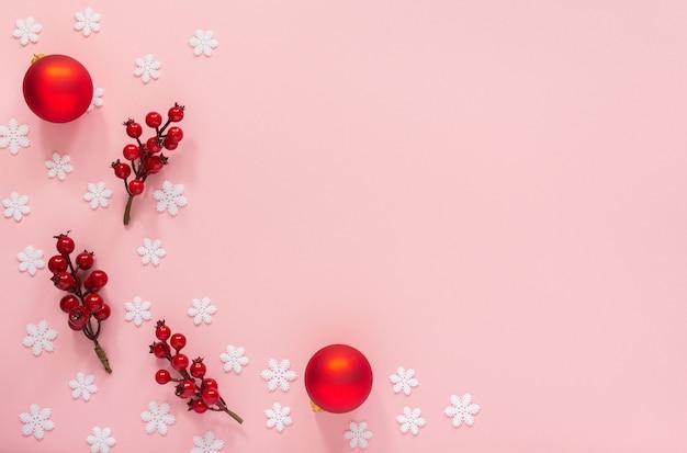 Fond de vacances, brindilles d'aubépine et boules de noël sur fond rose avec des flocons de neige, mise à plat, vue du dessus