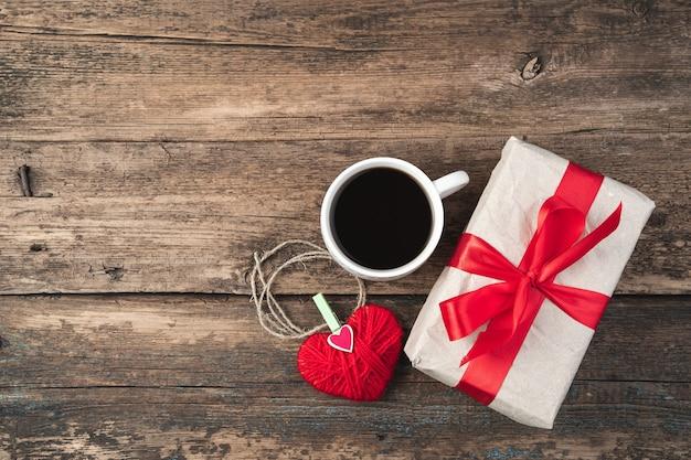 Fond de vacances avec cadeau, café et coeur sur bois. vue de dessus