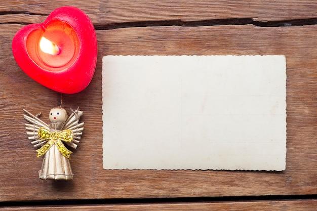 Fond de vacances avec carte postale vintage vierge, bougie allumée et ange jouet