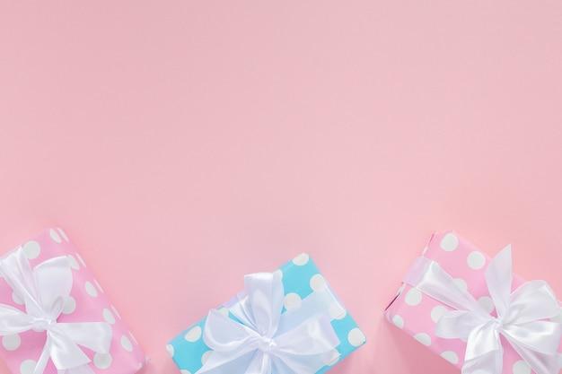Fond de vacances, coffrets cadeaux roses et bleus à pois avec ruban blanc et arc sur fond rose, mise à plat, vue de dessus, anniversaire ou saint valentin