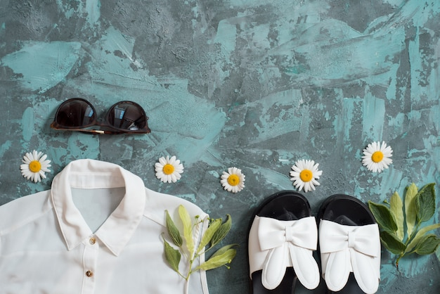 Fond de vacances d'été, accessoires pour femmes à la plage plate: chapeau de paille, bracelets, sandales en cuir, lunettes de soleil, perles et étoiles de mer sur table bleue.