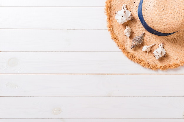 Fond de vacances d'été avec chapeau de paille et coquillages sur fond de bois vue de dessus avec espace de copie.