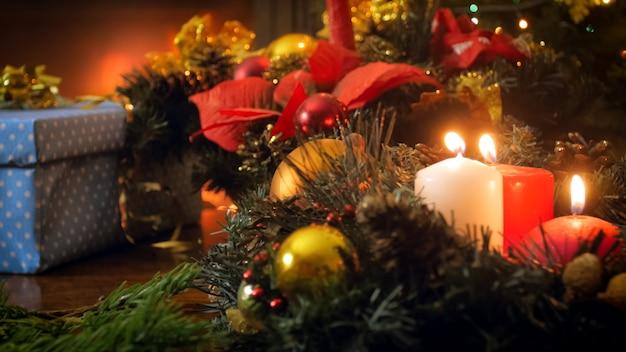 Fond de vacances d'hiver. bougies de noël brûlant sur une couronne de l'avent à côté de coffrets cadeaux colorés