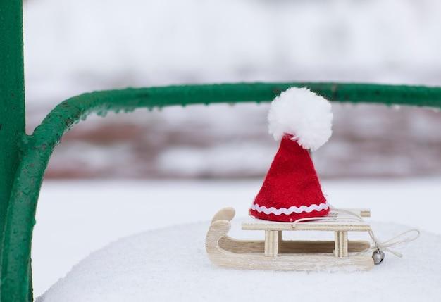 Fond de vacances d'hiver : chapeau de père noël sur un traîneau en bois. fermer