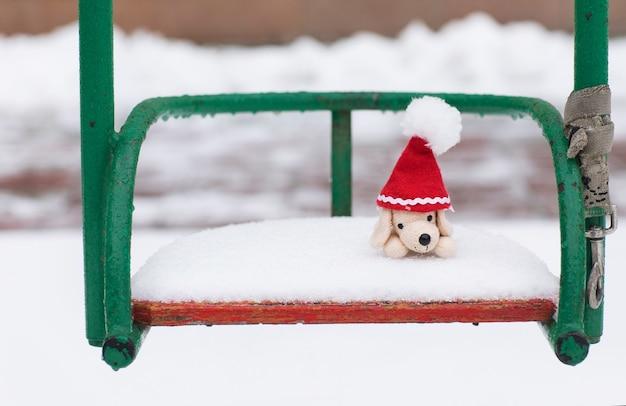Fond de vacances d'hiver : petit chien en peluche en bonnet de noel sur une balançoire enneigée. fermer