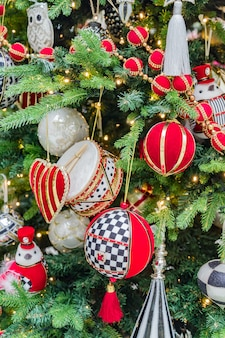 Fond de vacances de noël et du nouvel an. sapin de noël décoré de boules rouges, de jouets et de guirlandes. scintillant et pétillant. concept de célébration