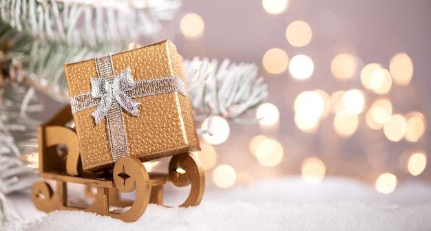 Fond de vacances de noël avec espace de copie pour le texte. cadeau d'or de noël sur le traîneau du père noël près d'un sapin avec de la neige et des lumières. bannière panoramique