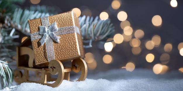 Fond de vacances de noël avec espace de copie pour le texte. cadeau d'or de noël sur le traîneau du père noël près d'un sapin avec de la neige et des lumières la nuit. bannière panoramique