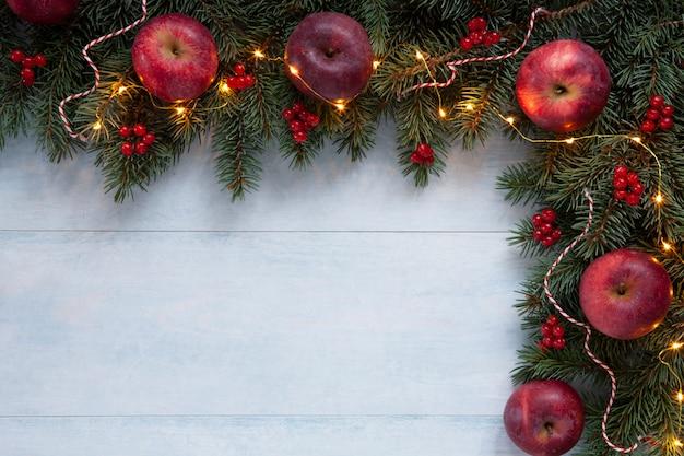 Fond de vacances de noël avec des pommes rouges, des fruits rouges et une guirlande lumineuse