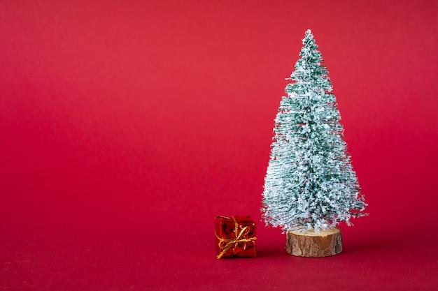 Fond de vacances de noël. sapin de noël couvert de neige et boîtes multicolores lumineuses avec des cadeaux. copiez l'espace.