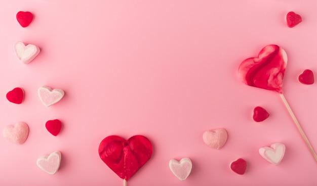Fond de vacances romantique rose avec des bonbons sucrés en forme de coeur. carte décorative pour la saint-valentin avec un espace pour le texte. thème amoureux.
