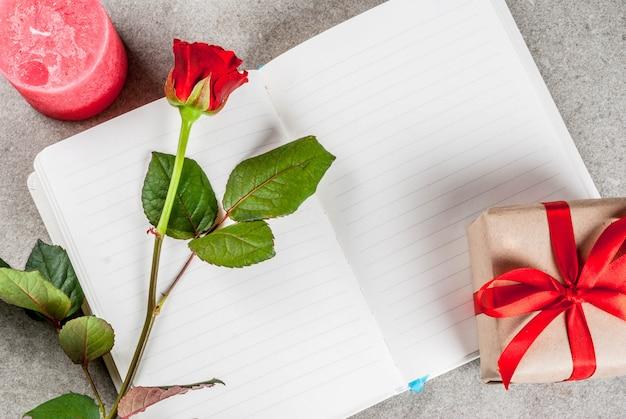 Fond de vacances, saint valentin. bouquet de roses rouges, cravate avec un ruban rouge, avec bloc-notes vierge, boîte-cadeau emballée et vue de dessus de bougie rouge