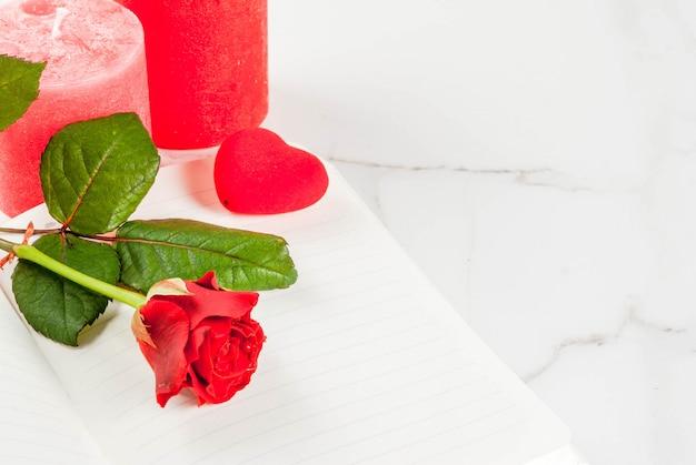 Fond de vacances, saint valentin. bouquet de roses rouges, cravate avec un ruban rouge, avec bloc-notes vierge, coffret cadeau enveloppé et bougie rouge. sur une table en marbre blanc