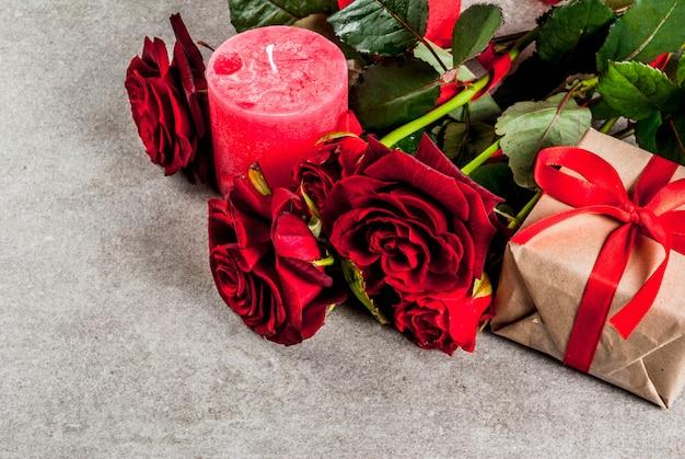 Fond de vacances, saint valentin. bouquet de roses rouges, cravate avec un ruban rouge, avec coffret cadeau enveloppé et bougie rouge