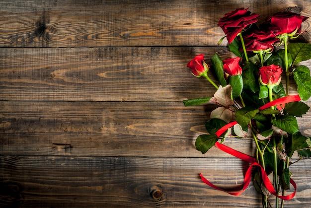 Fond de vacances, saint valentin. bouquet de roses rouges, cravate avec un ruban rouge. sur une table en bois