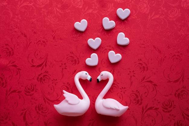 Fond de valentin avec oiseau flamingo couple sur fond rouge.