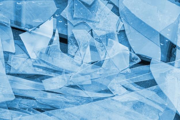 Fond de verre brisé sur le sol dans des tons bleus.