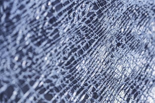 Fond de verre cassé. fenêtre en verre fissurée de toiles d'araignées.