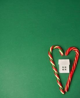Sur un fond vert, le cœur au centre duquel se trouve la maison blanche, le concept d'amour pour la maison et d'en prendre soin. photo de haute qualité