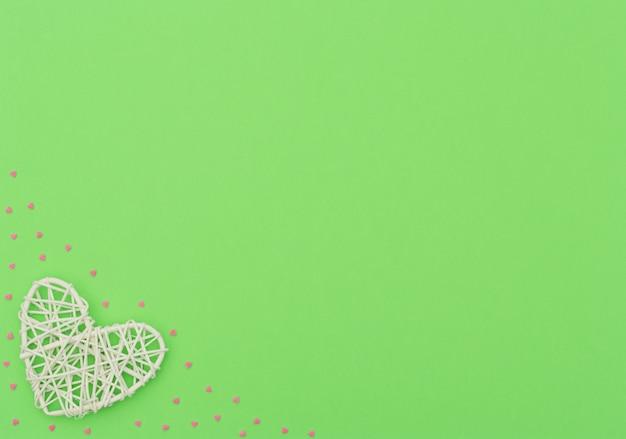 Fond vert de la saint-valentin avec rotin blanc et petits coeurs roses