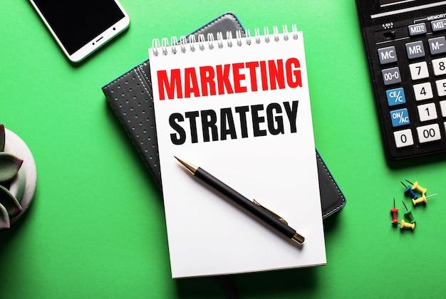 Sur fond vert - un téléphone, une calculatrice et un agenda avec l'inscription marketing strategy