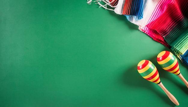 Fond vert de vacances cinco de mayo fabriqué à partir de rayures de couverture mexicaine maracas ou poncho