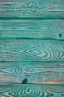 Fond vertical de planches de bois texturées peintes avec de la peinture verte.