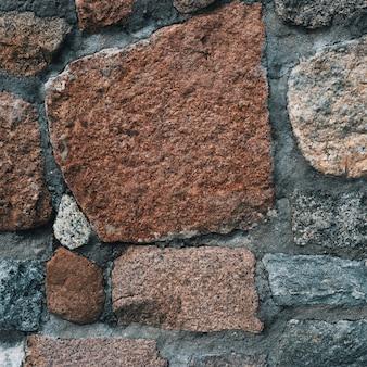 Fond de vieux mur de pierre avec des pierres de différentes tailles et couleurs
