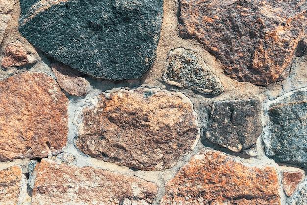 Fond de vieux mur de pierre avec des pierres.
