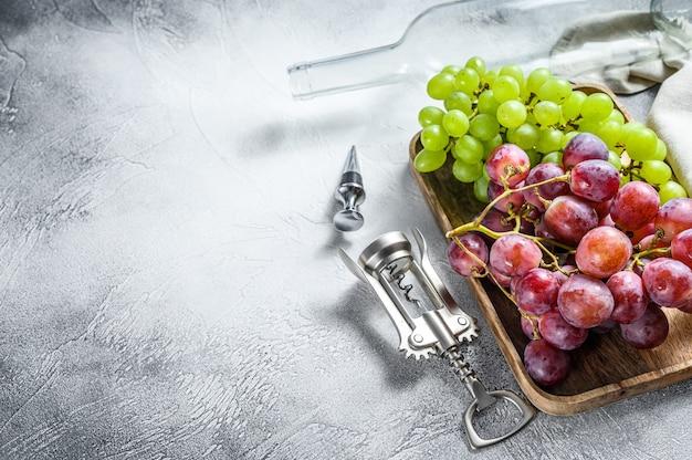Fond de vin. une branche de raisins verts et rouges, une bouteille vide, un tire-bouchon et un bouchon. concept de vinification à domicile. fond blanc.