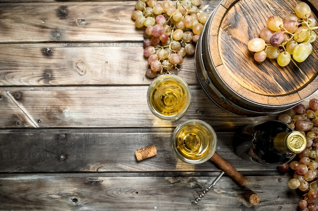 Fond de vin. vin blanc dans un vieux tonneau sur une table en bois