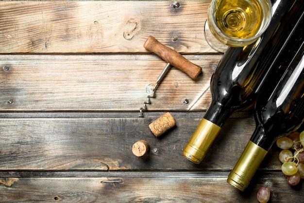 Fond de vin. vin blanc avec des rameaux de raisins frais. sur un fond en bois.