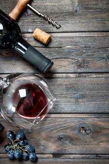 Fond de vin. vin rouge avec des raisins sur une table en bois.