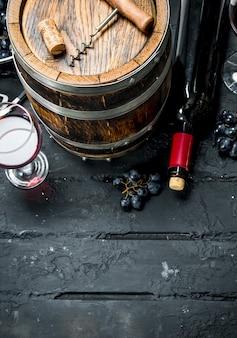Fond de vin. vin rouge avec des raisins et un vieux tonneau. sur un fond rustique noir.