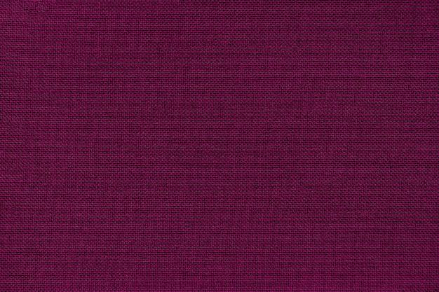 Fond violet foncé d'un matériau textile.