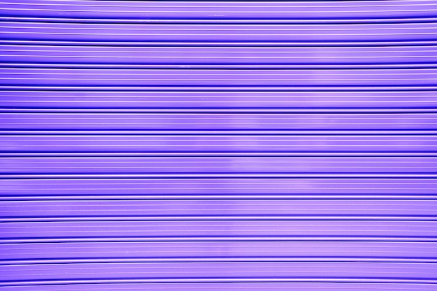 Fond violet d'un mur en métal avec des lignes horizontales, couleur féministe.