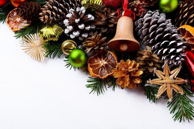 Fond de voeux de noël avec clochette en bois et cônes de pin à la main