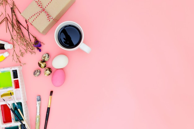 Fond de vue de dessus et jeu de peinture préparant pour pâques sur fond rose, oeufs de pâques