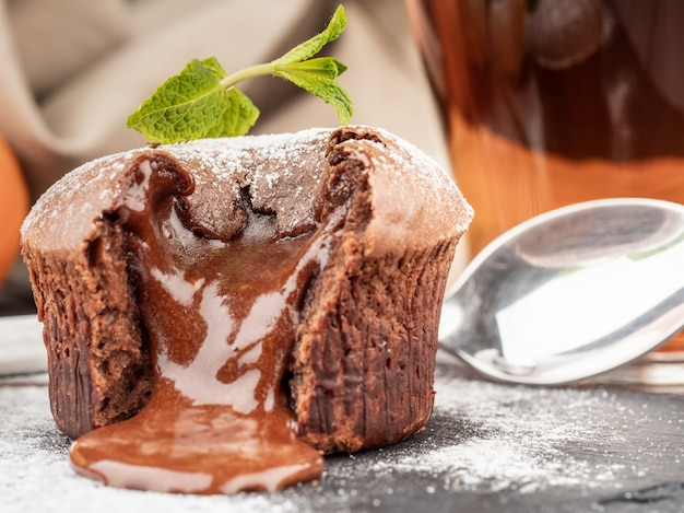 Fondant au chocolat avec garniture au chocolat qui coule sur une table avec une tasse de thé.