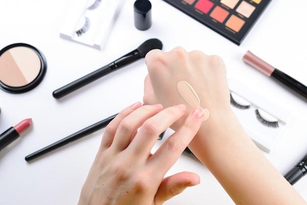 Fondation dans les mains de la femme. produits de maquillage professionnels avec produits de beauté cosmétiques, fond de teint, rouge à lèvres, ombres à paupières, cils, pinceaux et outils.