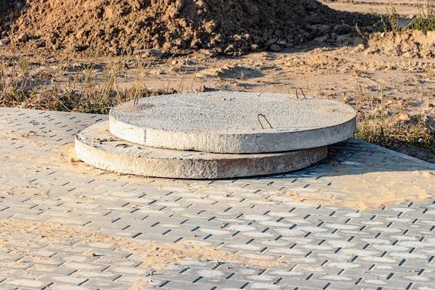 Les fonds de la fosse et des égouts en béton armé se trouvent à l'extérieur. produits en béton armé sur chantier. installations de production industrielle pour les puits d'égout.