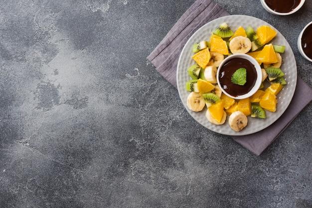 Fondue au chocolat avec des fruits sur un béton foncé
