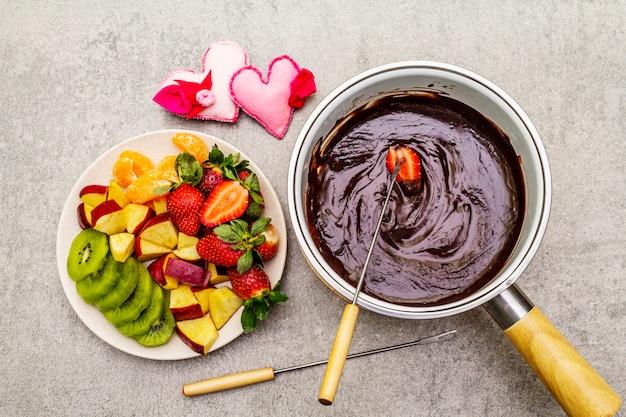 Fondue au chocolat. fruits frais assortis, deux types de chocolat, coeurs en feutre. ingrédients pour la cuisson d'un dessert romantique sucré.